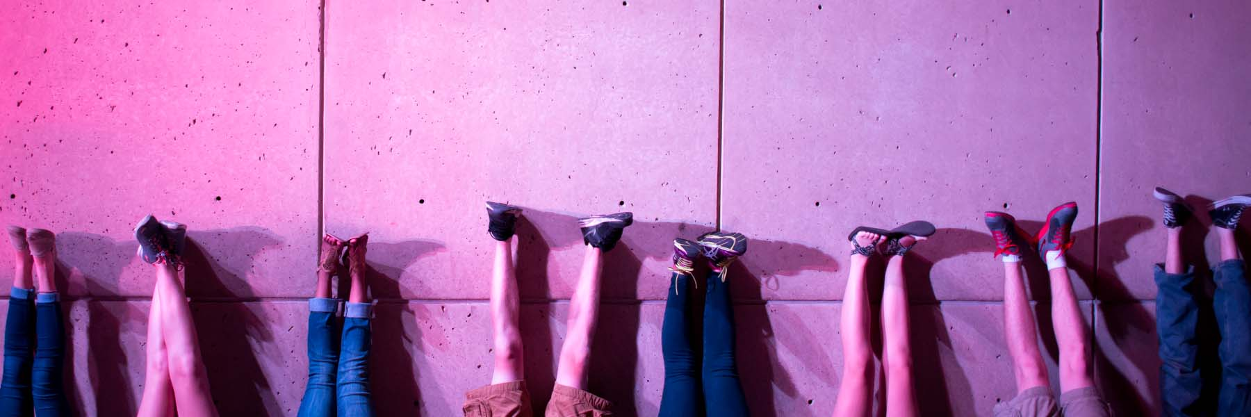 Students lie with their feet on the IU Art Museum wall in the pink glow of the light totem.