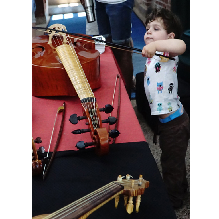 child playing at the instrument petting zoo